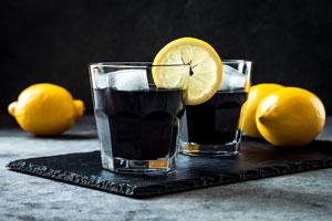 Två glas fyllda med detox av aktivt kol. På bilden syns även citronskivor