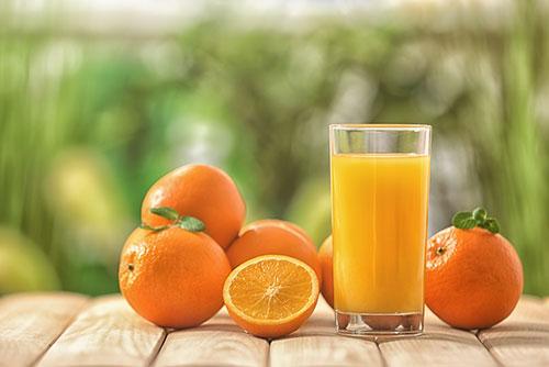 glas med apelsinjuice och apelsiner pa ett bord mot gron bakgrund