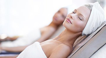 tva kvinnor i handdukar ligger avslappnande pa solstolar