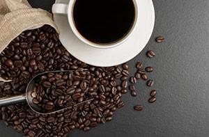 en kopp med kaffe och utspridda kaffebönor