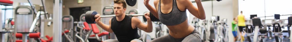 En kille som håller i en termos eller proteinshake i sitt hem med produkter som aminosyra på köksbänken