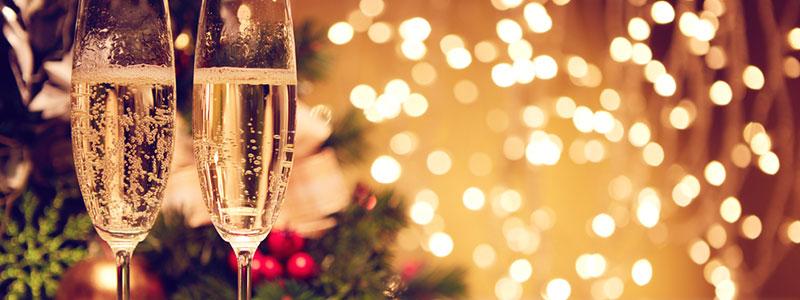 Bild på tva champagneglas med en julgran i brkagrunden och massvis med lampor och belysning