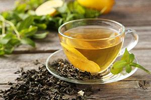 en kopp grönt te omgiven av färska teblad