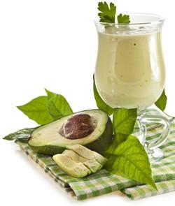 ett glas pa en rutig duk med en gron vatska i och en avokado
