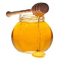 en glasburk fylld med honung med en traslev som droppar honung pa den mot en vit bakgrund