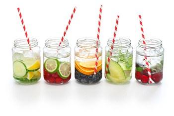 Fem stycken farglada och frascha drinkar i genomskinliga glas star uppradade