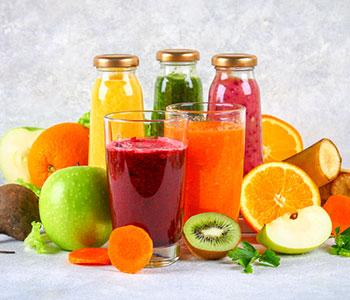 tva hoga glas med rod och orange juice i mot en vit bakgrund omringad av olika exotiska frukter