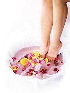 ett fotbad fyllt med rosa blommor, rosa vatten och citronskivor