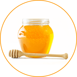 en glasburk fylld med honung med en traslev som ligger framfor mot en vit bakgrund