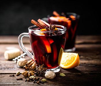 Två koppar glogg i genomskinliga koppar är redo att drickas. Bredvid kopparna syns bade kanel och apelsin