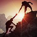 Tva personer klattrat uppfor ett berg. Den ena hjalper den andra upp pa toppen i motljus, i solnedgangen.