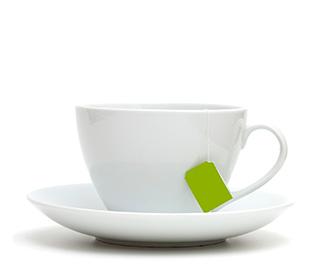 En vit kopp med tillhörande fat syns mot en vit bakgrund. Koppen innehåller en tepåse.