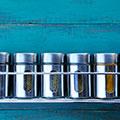 flera metallburkar med kryddor star pa en hylla mot en bla vagg