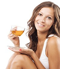 En kvinna som dricker detoxte i en genomskinlig kopp