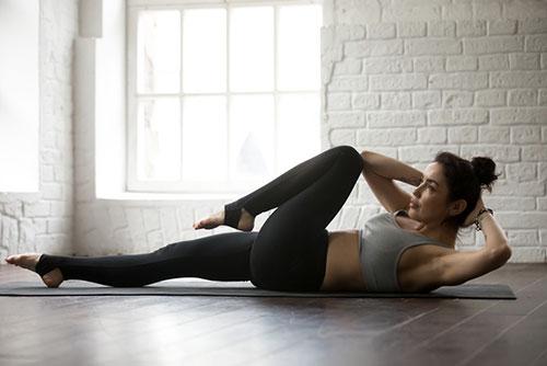 en kvinna pa golvet i taningsklader gor sneda sit ups