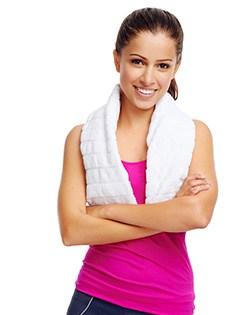 En kvinna i ett rosa tranisnlinne bär en handduk runt halsen och ler mot kameran med armarna i kors