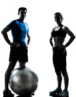 en kvinna och en man i traningsklader star med handerna pa hofterna i motljus med en traningsboll mellan sig