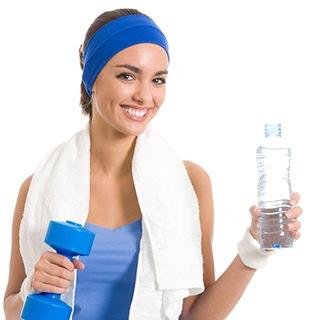 en kvinna i blaa traningsklader med en handduk runt halsen haller i en bla hantel och en vattenflaska