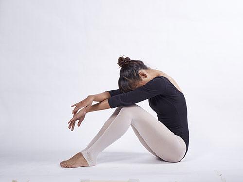 en kvinna i body och leggings sitter pa golvet med haret uppsatt mot en vit bakgrund