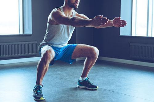 en man i blaa shorts och gratt linne gor knaboj, squats