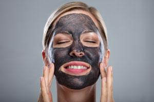 En kvinna som har använt en ansiktsmask gjord av aktivt kol