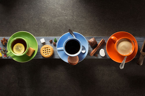 gron mugg med te, bla mugg med kaffe, organge mjolk med kaffe star pa en bla planka. Kakor och choklad ligger runtom.