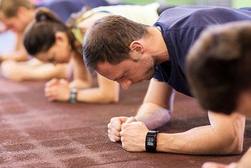 flera gymdeltagare i traningsklader gor plankan pa golvet