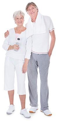 en aldre man och en aldre kvinna i traningsklader posear for kameran