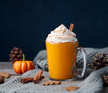 En Pumpkin Spiced Latte, serverad i ett genomskinigt glas. I bagrunden ser man en pumpa, kotte och en gra filt