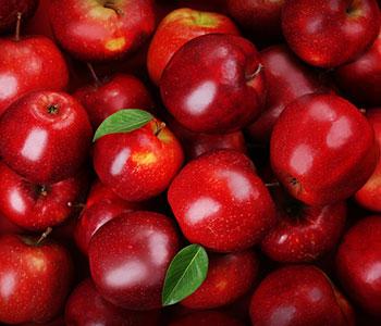 Bild på massvis med roda applen som ligger på varandra i en hog