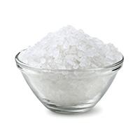 En genomskinlig skal med salt som är fyllt till kanten med detta kristalliknande amne. Vit bakgrund