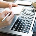 en person skriver i ett anteckningsblock samtidigt som den sitter framfor datorn