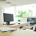 ett kontor med ett brunt skrivbord dar det star en dator och ligger papper
