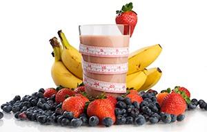 Ett glas med smoothie star i en hog jordgubbar, blabar och bananer. Ett mattband runt glaset. mot vit bakgrund