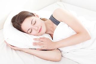 en sovande kvinna ligger i vita sangklader mot en vit bakgrund