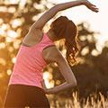 En bild på en kvinna i traningsklader som stretchar utomhus i solnedgangen