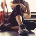 Bild på en kvinna i traningsklader som stretchar efter ett traningspass på gymmet