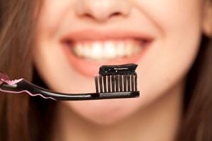 En bild på en kvinna som håller upp en tandborste med svart tandkräm av aktiverad kol