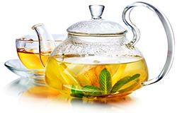 En genomskinlig tillbringare med te och ett matchande glas syns mot en vit bakgrund