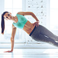 En kvinna i traningsklader tranar armar och hofter
