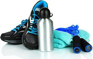 svarta gympaskor, en stålvattenflaska, gron handduk och blatt hopprep mot en vit bakgrund