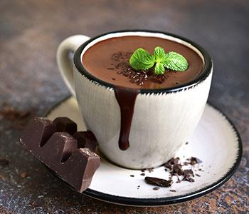 En kopp varm choklad med ett myntablad ovanpa. Bredvid koppen ligger nagra bitar mork choklad
