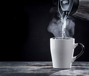 En tekanna haller upp kokande vatten i en temugg som star på en morkgra bank