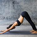 En kvinna star i en yogaposition i traningsklader på en yogamatta