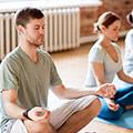 Man och kvinna i traningsklader sitter på varsinn yogamatta och slappnar av