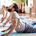 En traningsklass utfor yogaovningar i traningsklader på yogamattor